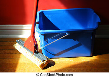 mop and bucket - mop and blue bucket on hardwood floors with...