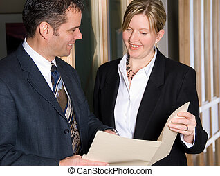 Reviewing files - two business people looking at some files
