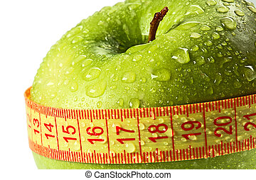 green apple with water drops is measured