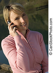 phone - young blond women calling by mobile phone outside