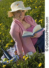book - young women with hat reading a book outside