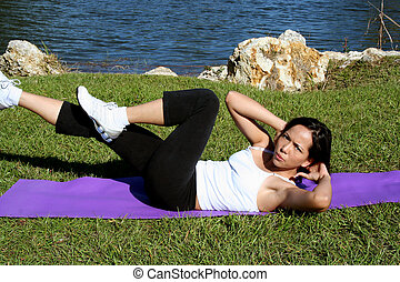 Bicycle Crunches - Woman doing bicycle crunches outside near...
