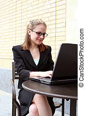 Tiffany 22 - businesswoman working at computer at an outside...