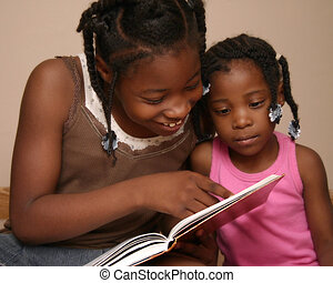 Reading to Sister - Big sister reading to little sister.