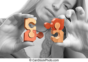 Business solution - Young woman bringing together puzzle...
