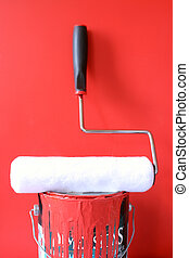painting supplies - paint roller on top of red paint can for...