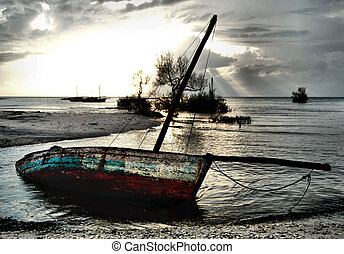 Red and White Dhow Sailing boat stranded at low tide in...