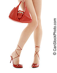 long legs on high heels and red purse over white