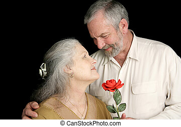 Rose for His Wife - A beautiful mature woman receiving a red...