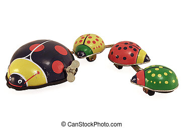 Lady Bug Family - An antique tin toy lady bug with her...