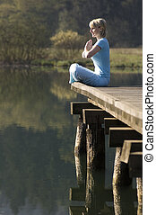 yoga - young girl relaxing on pier in early morning