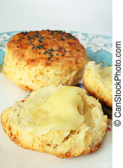 Buttered scone - Two scones, one cut and buttered, on an...