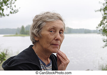 Portrait of elderly woman at the lake side