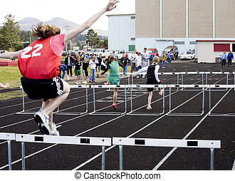 Girls\\\' 100 Meter Hurdles - Photo of a girl jumping over a...