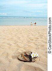 Beach vacation - A pair of sandals and sunglasses on a...