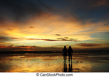 Sunset beach - Two people in silhouette walking on a beach...