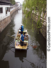 Suzhou Canal - Workers on a canal in Suzhou cleaning the...