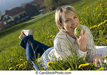 apple - young woman eating apple outside on field