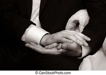 Groom and dride - Female hands in mans hands on a dark...