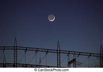 Moon over Power Masts - A crescent moon hanging lower of the...