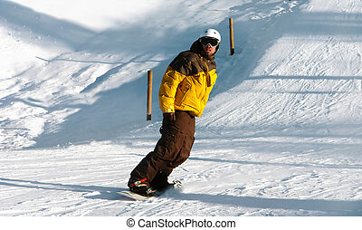 Snowboarder - Young Man snowboarding down a mountain
