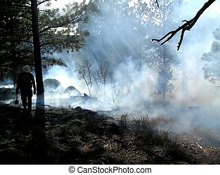 End of the Day - Fire fighter with tool after igniting...