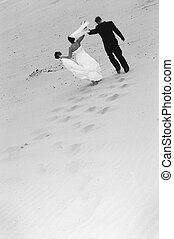 Newlyweds walking down beach
