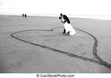 Newlyweds - Couple kissing on beach standing inside of heart...