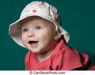 Baby in Hat - A baby in a fish print hat smiling and looking...