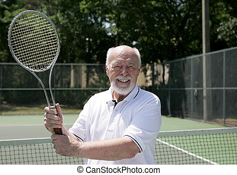 Senior Man Plays Tennis - A handsome senior man on the...