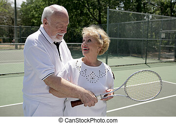 Active Seniors Play Tennis - A senior couple playing tennis...