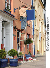 Renovations - Middle aged man up a ladder hanging a new blue...