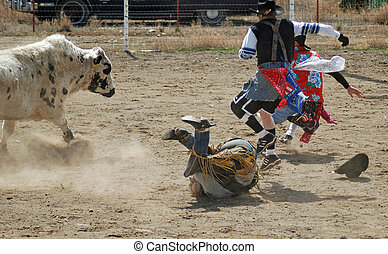 Bull rider on ground with rodeo clowns protecting him.