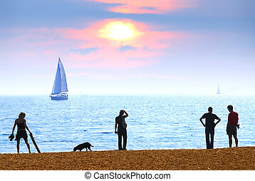 Beach sunset - People on a beach watching scenic sunset