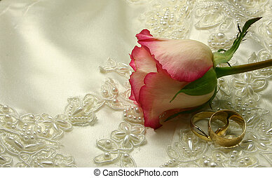 roses and rings on a bridal gown - wedding rings and a rose...