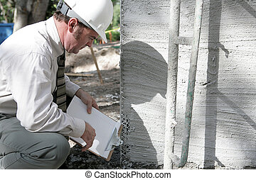 Building Inspector Checks Foundation - A building inspector...