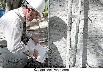 Building Inspector Checks Foundation - A building inspector...