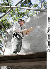 Building Inspector on Scaffolding - A building inspector on...
