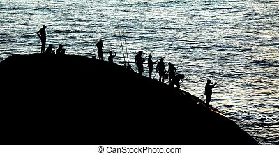 Anglers at sunset - Silhouetted anglers gathered on a rock...