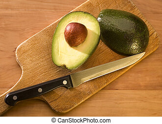 avocado - Avocado fruit halves on a chopping board