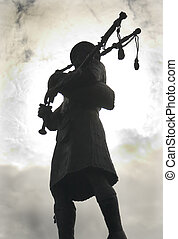 Bagpiper in high contrast - A Scottish bagpiper plays his...