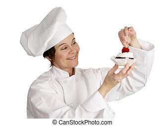 The Finishing Touch - A pastry chef putting a strawberry on...
