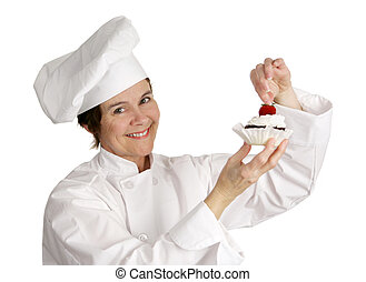 Chef Putting Strawberry on Top - A pastry chef putting a...