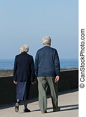 Enjoying a Stroll - Elderly couple walikng together on a...