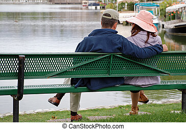 Couple by the Lake - Look - A couple sit on a bench by a...