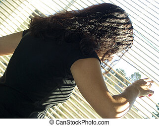 Curious girl - Young woman looking through blinds out of the...