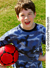 Boy with soccer ball - Young cute happy boy holding a red...