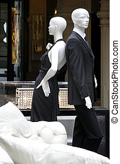 shop of fashionable clothes - Pair dummies in a show-window...