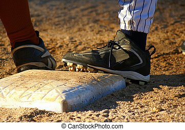 On Base - Close up of feet from two baseball players on...