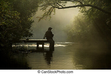 misty river fisherman - A lone fly fisherman, with full...